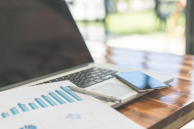 Gráficos financeiros sobre a mesa com laptop. (imagem filtrada pr Foto gratuita