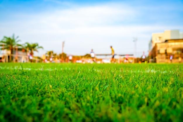 Grama no campo de futebol com fundo de futebol de jogador de borrão. Foto Premium