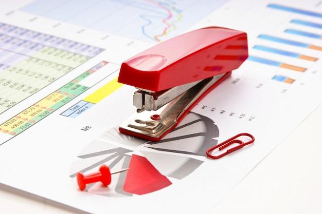 Grampeador e papel de trabalho com um diagrama Foto Premium
