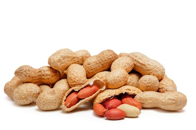 Grande amendoim descascado close-up de feijão com casca isolado no branco Foto Premium