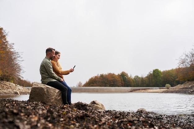 Grande angular para um casal sentado em frente ao lago, olhando para o celular ao ar livre com um lago Foto Premium