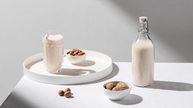 Grande ângulo da garrafa de leite com vidro na bandeja e nozes Foto gratuita