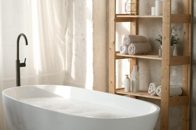 Grande banheira de porcelana branca cheia de água e espuma por prateleiras de madeira com toalhas enroladas e potes de plástico contra a parede do banheiro Foto Premium
