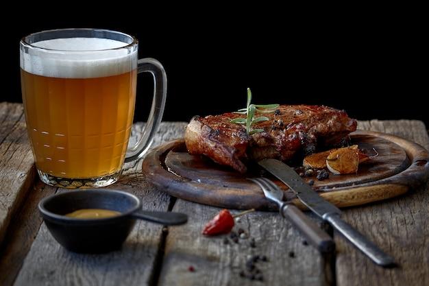 Grande bife frito, copo de cerveja, mostarda e talheres em uma mesa de madeira velha Foto Premium