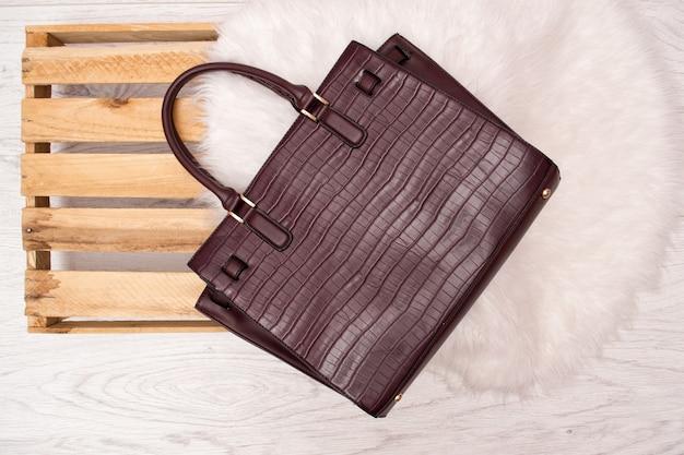 Grande bolsa preta em um palete e pelo branco. Foto Premium