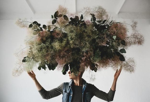 Grande buquê decorativo feito de folhas verdes e musgo paira sobre a cabeça do homem Foto gratuita