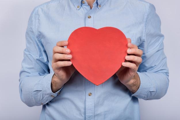 Grande caixa vermelha em forma de coração nas mãos masculinas. presente para amado. presente para dia dos namorados Foto Premium