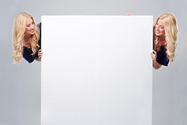 Grande cartaz vazio e duas irmãs Foto gratuita