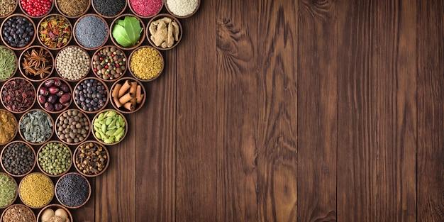 Grande conjunto de especiarias em uma mesa de madeira, vista superior Foto Premium