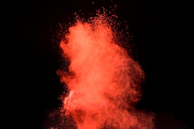 Grande explosão vermelha de pó no fundo escuro Foto gratuita