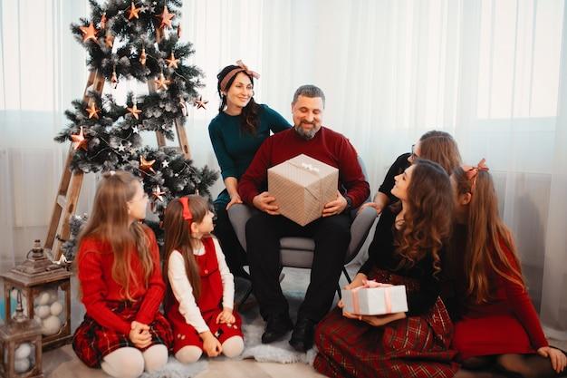 Grande família sentada em casa perto de árvore de natal Foto gratuita