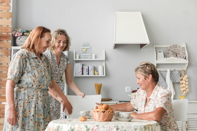 Grande, filha, organizando, cadeira, para, dela, vovó, em, cozinha Foto gratuita