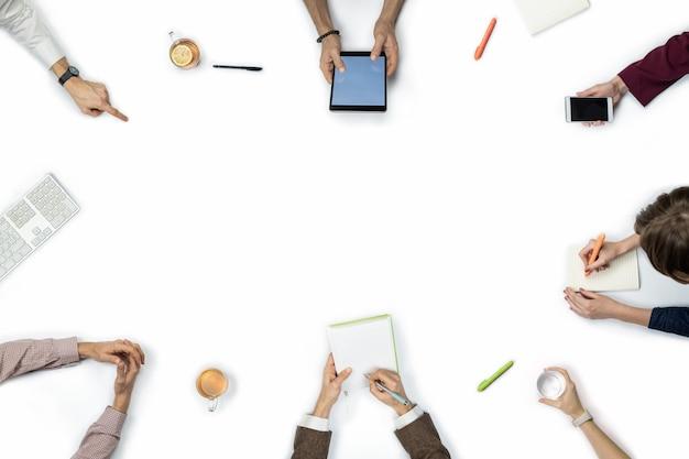 Grande grupo de pessoas na reunião de negócios, vista superior. postura plana com espaço de cópia de diversas pessoas as mãos em torno de uma mesa. Foto Premium