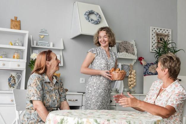 Grande mãe mãe, olhar, sorrindo, filha, segurando, cesta vime, de, croissant Foto gratuita