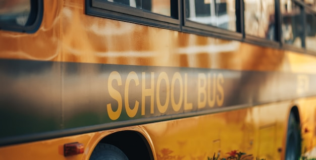 Grande ônibus escolar amarelo, volta às aulas, entrega das crianças à escola Foto Premium