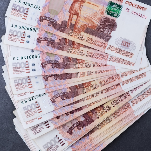 Grande pilha de notas de dinheiro russo de cinco mil rublos mentindo fã sobre um fundo cinza de cimento. Foto Premium