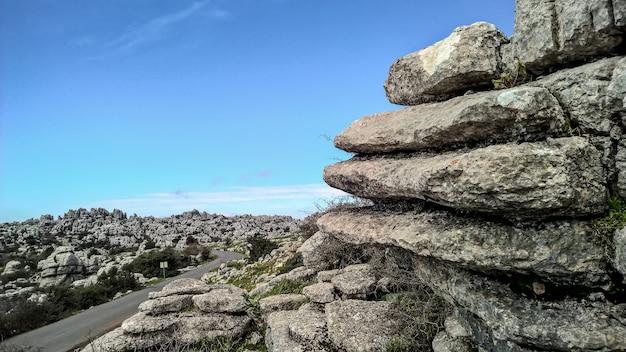 Grande plano de camadas de rochas e um céu claro e brilhante ao longo de uma estrada de asfalto liso Foto gratuita