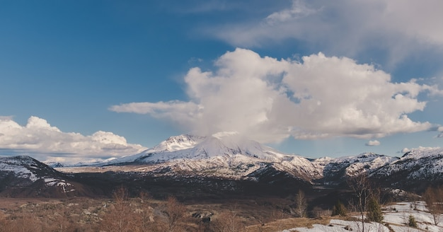 Grande plano de montanhas nevadas à distância sob um céu azul nublado Foto gratuita