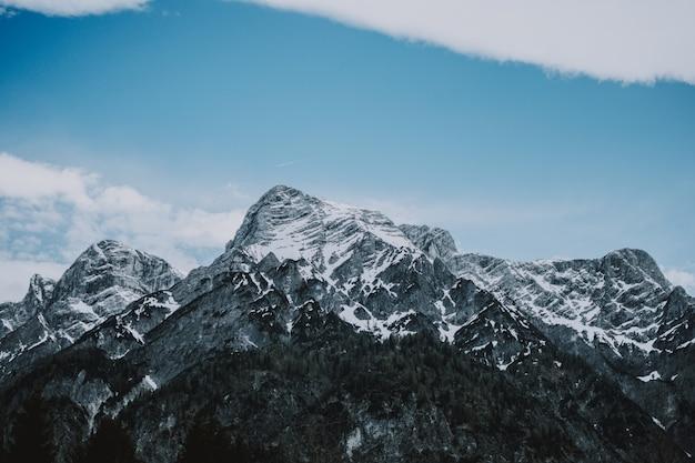 Grande plano de montanhas rochosas cobertas de neve e o lindo céu azul ao fundo Foto gratuita