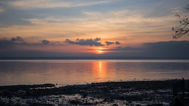 Grande plano de um mar sob um céu com nuvens durante o pôr do sol Foto gratuita