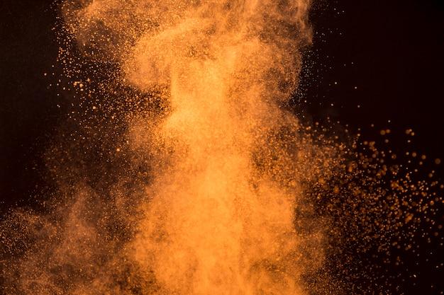 Grande respingo de pó de maquiagem laranja em fundo escuro Foto gratuita