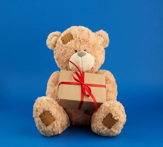 Grande urso de pelúcia bege segura uma caixa embrulhada em papel pardo Foto Premium