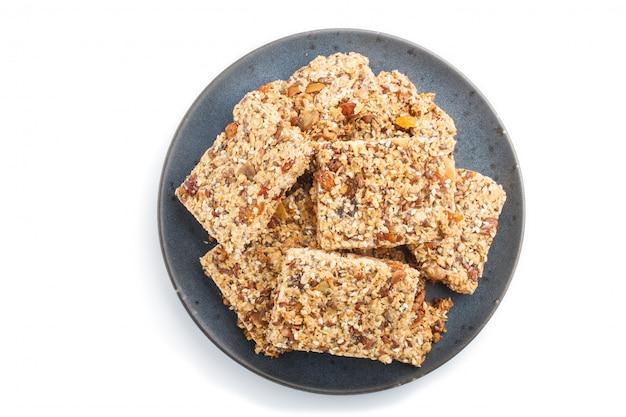 Granola caseira de flocos de aveia datas secas damascos passas nozes no prato de cerâmico azul isolado no fundo branco Foto Premium