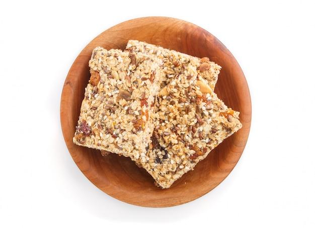 Granola caseira de flocos de aveia, tâmaras, damascos secos, passas, nozes na placa de madeira marrom isolada. vista do topo. Foto Premium