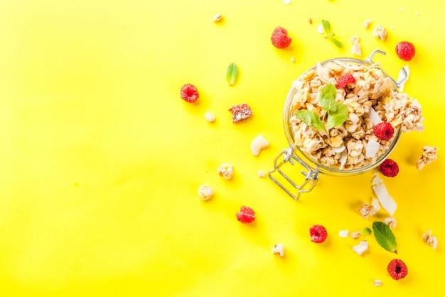 Granola caseira saudável de café da manhã e lanche conceito com framboesas frescas em jar em fundo amarelo brilhante Foto Premium