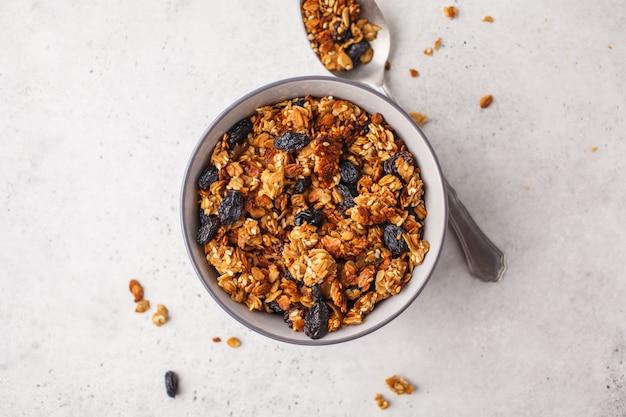 Granola cozido com as passas na bacia, fundo branco. Foto Premium