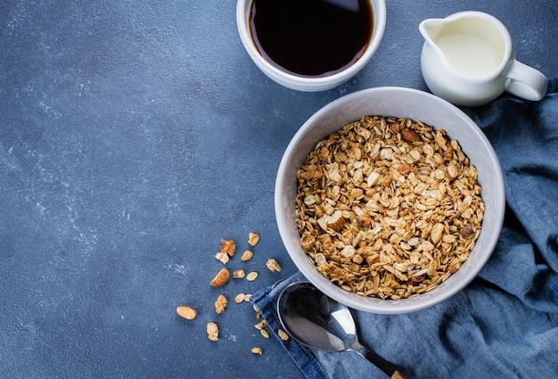 Granola do café da manhã, leite ou iogurte e mel na bandeja de madeira no fundo de pedra da tabela. vista do topo Foto Premium