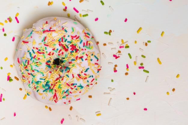 Granulado colorido sobre o donut branco contra o pano de fundo branco Foto gratuita