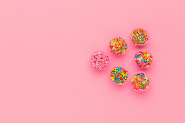 Granulado de açúcar, decoração para bolo e sorvete e biscoitos no fundo rosa Foto Premium