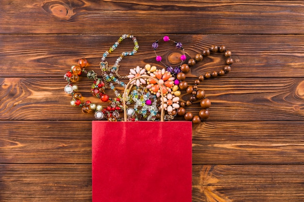 Grânulos de jóias e saco de papel vermelho sobre fundo de madeira Foto gratuita