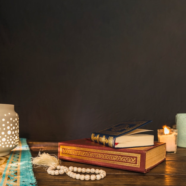 Grânulos e livros perto de lanterna e vela Foto gratuita