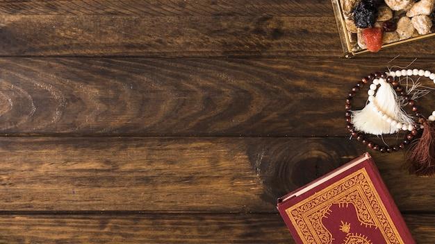 Grânulos perto de livro religioso e doces Foto gratuita