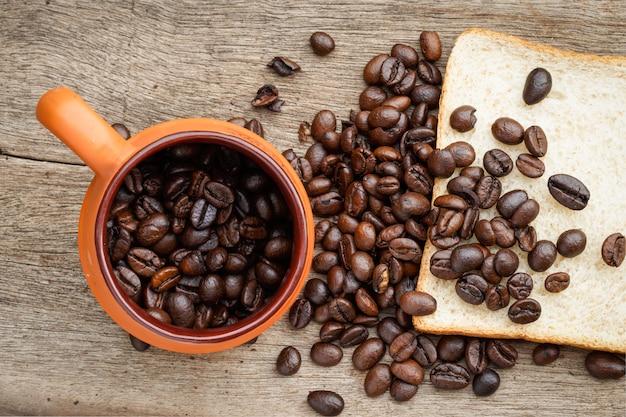 Grão de café no chão de madeira Foto Premium