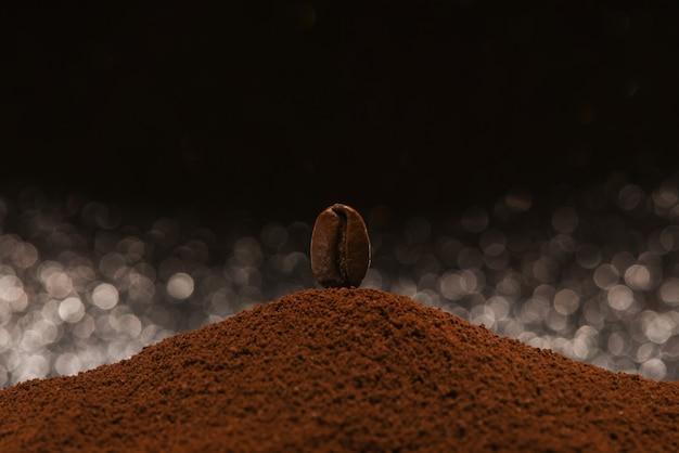 Grão de café torrado fresco fica em um punhado de café moído em um fundo preto e branco bokeh Foto Premium