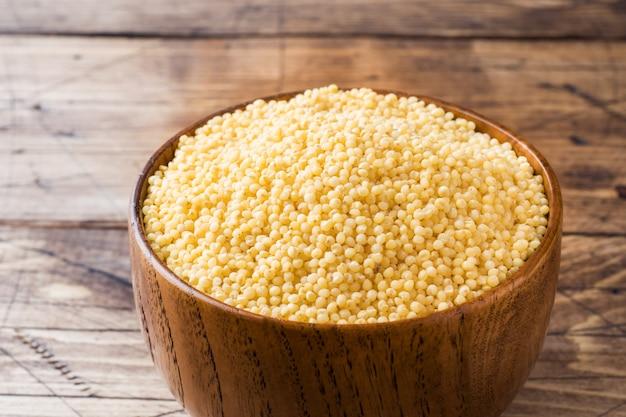 Grão de milho cru em uma tigela de madeira sobre uma mesa de madeira rústica. Foto Premium