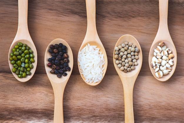 Grãos colocados em 5 colheres coloque na mesa de madeira Foto Premium