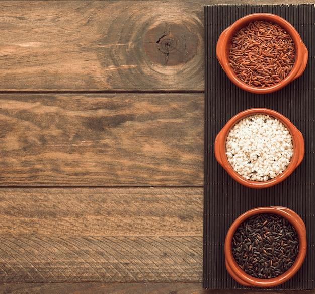 Grãos de arroz orgânico marrom e branco tigelas na bandeja sobre a mesa de madeira Foto gratuita