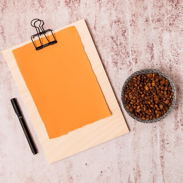 Grãos de café, caneta e prancheta Foto gratuita