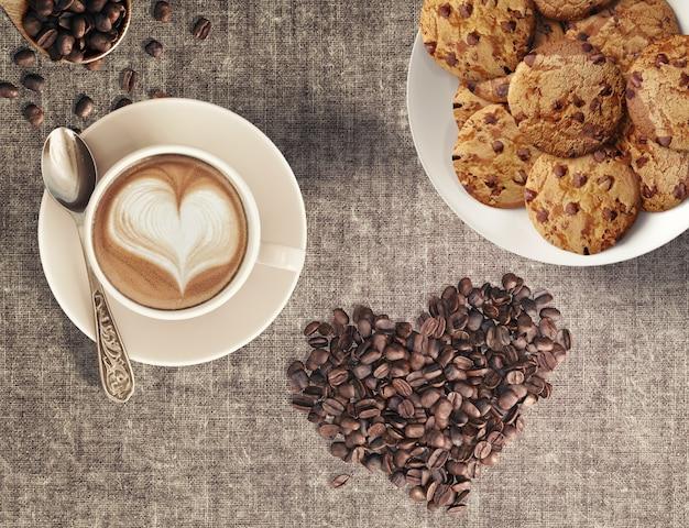 Grãos de café capuccino em forma de coração e biscoitos de chocolate caseiro em uma casa de café Foto Premium