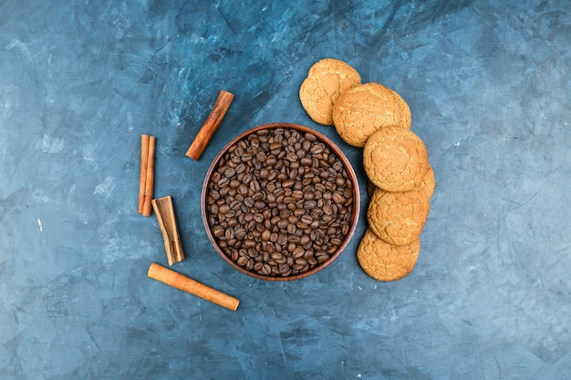 Grãos de café com biscoitos em fundo azul escuro Foto gratuita