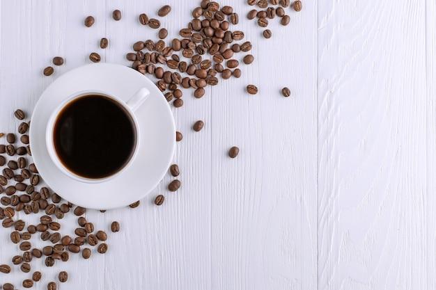 Grãos de café dispersados, um copo e chocolate preto em uma mesa de madeira branca. copie o espaço. Foto Premium
