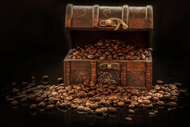 Grãos de café e baú velho em fundo preto - the black gold Foto Premium