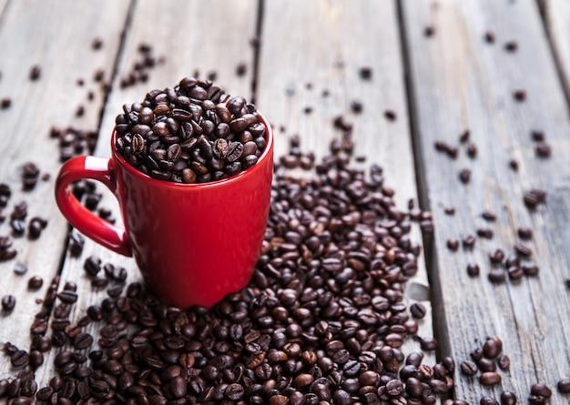 Grãos de café e xícara de café vermelha na mesa de madeira. Foto Premium