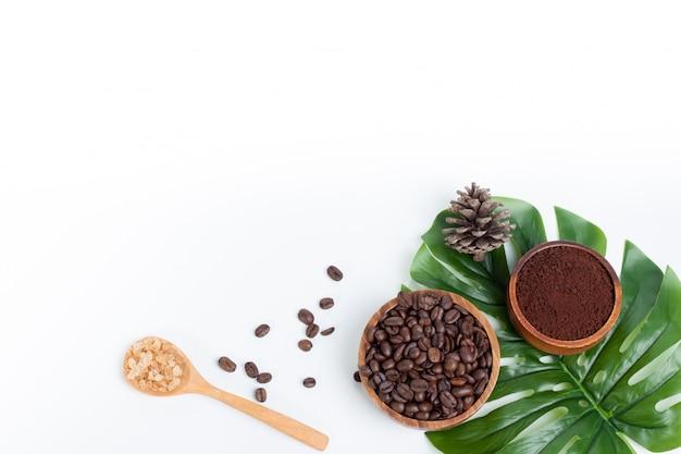 Grãos de café em folhas verdes de açúcar na colher de pau e pinho isolado Foto Premium