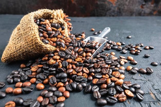 Grãos de café em um saco de pano marrom Foto Premium