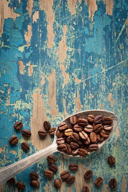 Grãos de café em uma colher de madeira Foto Premium